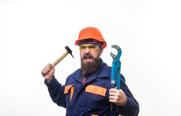 Homem barbudo com ferramentas de conserto na mão. trabalhador de serviço de conserto com capacete com chave de cachimbo. homem barbudo