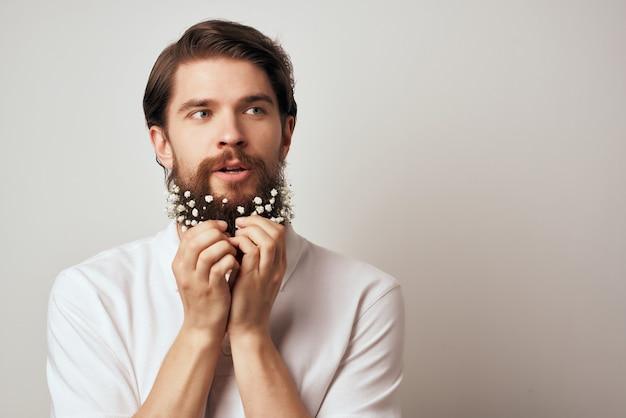 Homem barbudo com flores na barba em um close da camisa