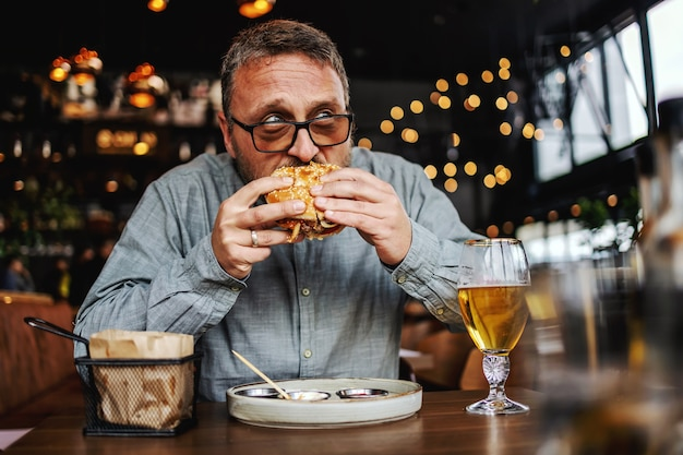 Homem barbudo com fome de meia idade sentado no restaurante e comendo um hambúrguer delicioso.