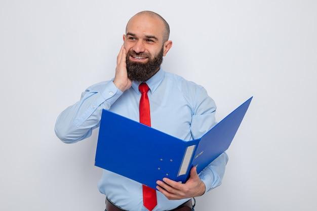 Homem barbudo com gravata vermelha e camisa azul segurando uma pasta do escritório e olhando com um sorriso no rosto feliz e animado