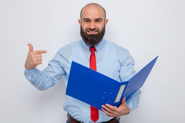 Homem barbudo com gravata vermelha e camisa azul segurando uma pasta do escritório e olhando em pé sobre um fundo branco