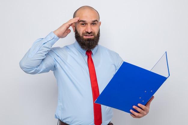 Homem barbudo com gravata vermelha e camisa azul segurando uma pasta do escritório, olhando para a câmera, feliz e animado com a mão na cabeça em pé sobre um fundo branco