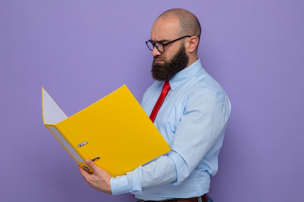Homem barbudo com gravata vermelha e camisa azul, usando óculos, segurando uma pasta do escritório e olhando com uma cara séria