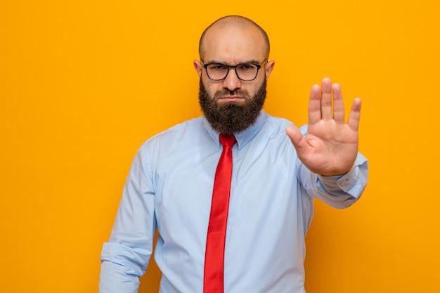 Homem barbudo com gravata vermelha e camisa usando óculos, olhando para a câmera com cara séria, fazendo gesto de parada com a mão em pé sobre fundo laranja