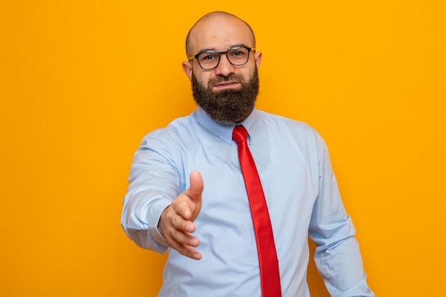 Homem barbudo com gravata vermelha e camisa usando óculos, olhando para a câmera, sorrindo amigável, oferecendo a mão fazendo um gesto de saudação em pé sobre um fundo laranja