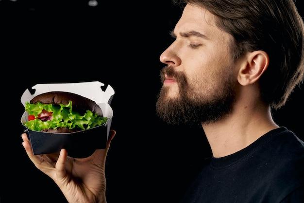 Homem barbudo com mãos de hambúrguer em restaurante gourmet de iguarias