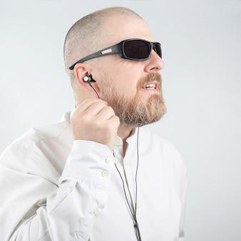 Homem barbudo com óculos escuros ouvindo música em fones de ouvido compactos