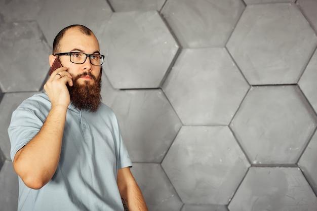 Homem barbudo com óculos, falando em um telefone celular.
