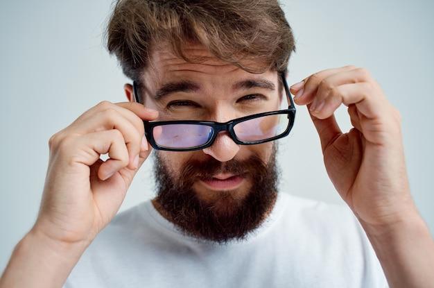 Homem barbudo com óculos na mão e problemas de visão.