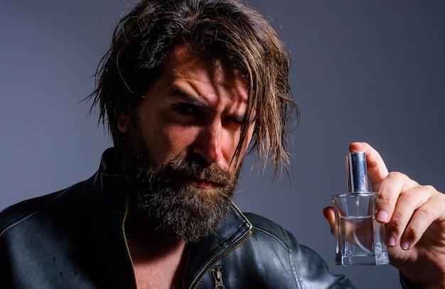 Homem barbudo com perfume. fragrância e perfumaria masculina. cara bonito com frasco de colônia. cosméticos masculinos.