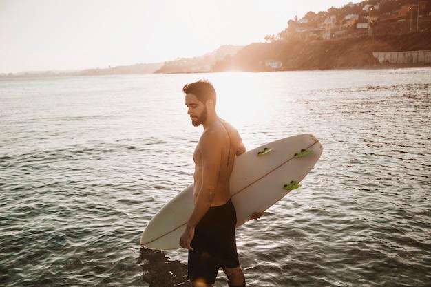 Homem barbudo com prancha de surf na praia perto da água no tempo ensolarado