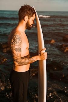 Homem barbudo com prancha de surf na praia perto da água