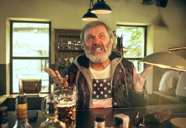 Homem barbudo com raiva, bebendo álcool no bar e assistindo a um programa de esporte na tv. aproveitando minha cerveja favorita. homem com uma caneca de cerveja, sentado à mesa. fã de futebol ou esporte. conceito de emoções humanas