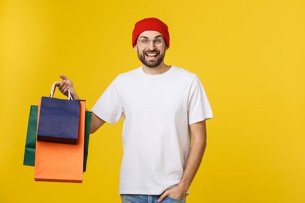 Homem barbudo com sacos de compras com sentimento feliz isolado no amarelo