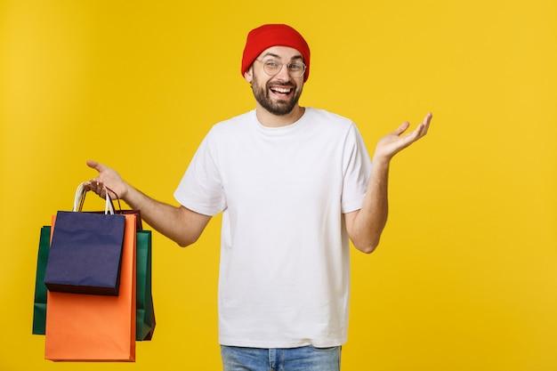 Homem barbudo com sacos de compras com sentimento feliz isolado no bacground amarelo