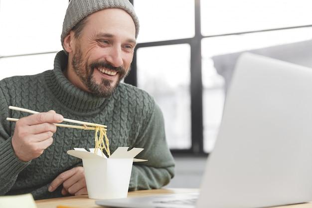 Homem barbudo com suéter de malha quente e chapéu almoçando