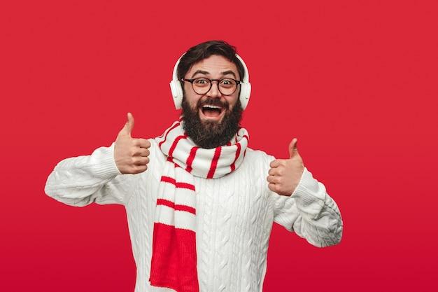 Homem barbudo com suéter e cachecol apontando o polegar para cima