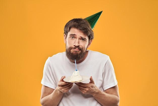 Homem barbudo com um bolo em um boné comemorando seu aniversário