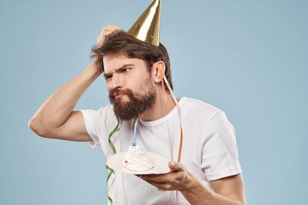 Homem barbudo com um boné em seu bolo de presente de férias de cabeça.