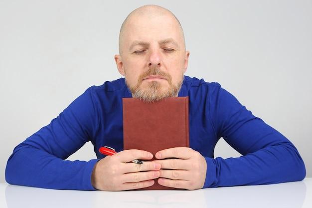 Homem barbudo com um caderno e uma caneta nas mãos pensa