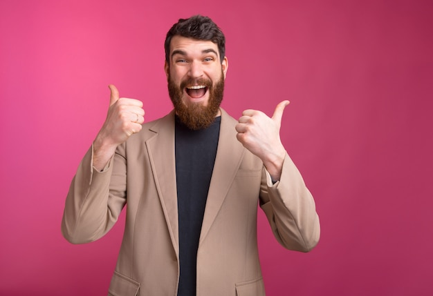 Homem barbudo com um grande sorriso, vestindo uma jaqueta está aparecendo os dois polegares em fundo rosa.