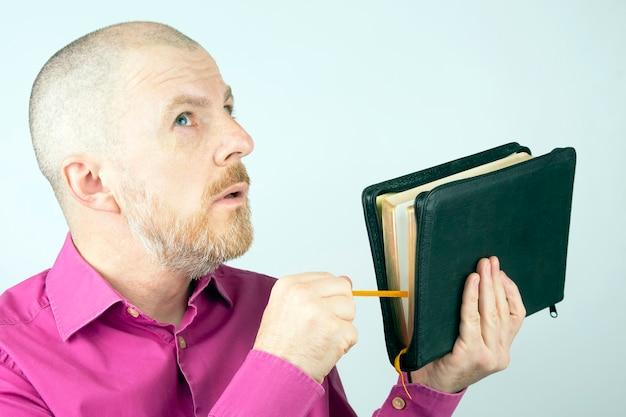 Homem barbudo com uma bíblia nas mãos olhando para cima
