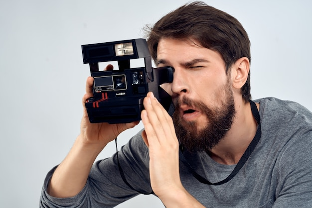 Homem barbudo com uma câmera nas mãos fotógrafos passatempo profissional