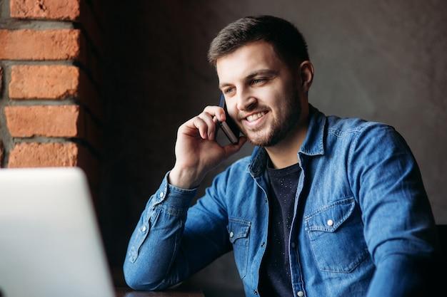 Homem barbudo com uma camisa jeans usando o telefone dentro de um restaurante