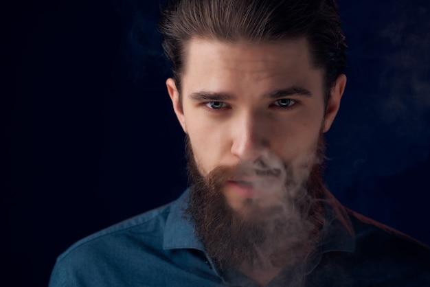 Homem barbudo com uma camisa preta nuvens de fumaça fundo escuro