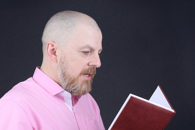 Homem barbudo com uma camisa rosa lendo um livro