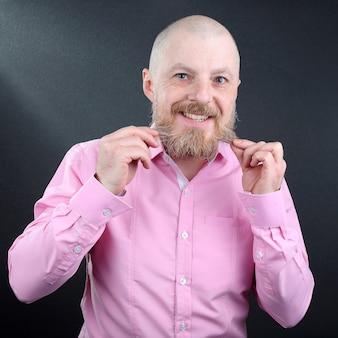 Homem barbudo com uma camisa rosa tocando a barba