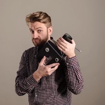 Homem barbudo com uma camisa xadrez segurando nas mãos uma câmera de filme antiga