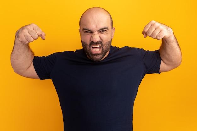Homem barbudo com uma camiseta azul marinho com cara de zangado levantando os punhos louco louco em pé sobre a parede laranja