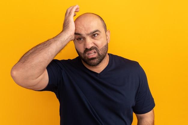 Homem barbudo com uma camiseta azul marinho parado olhando para o lado, confuso com a mão na cabeça por engano na parede laranja