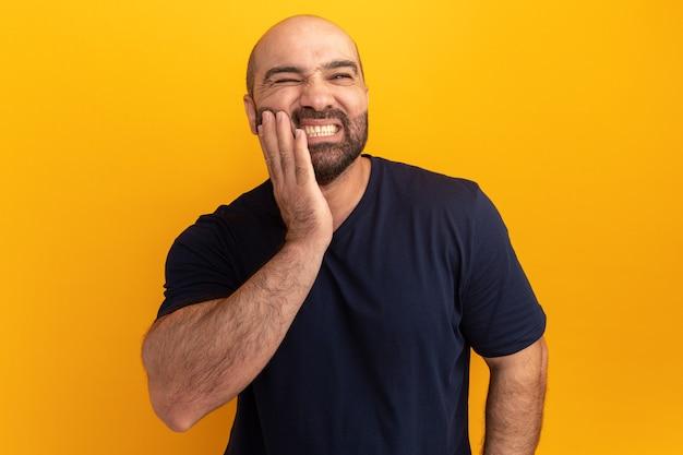 Homem barbudo com uma camiseta azul marinho parecendo doente tocando sua bochecha tendo dor de dente em pé sobre a parede laranja