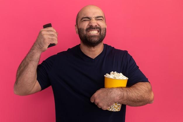 Homem barbudo com uma camiseta azul marinho segurando um balde de pipoca e o controle remoto da tv, parecendo aborrecido e irritado em pé sobre a parede rosa