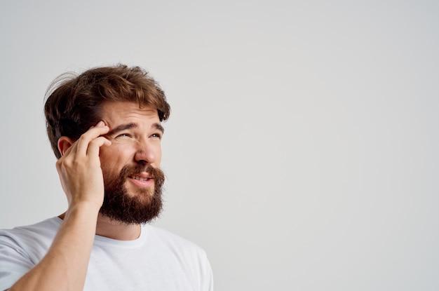 Homem barbudo com uma camiseta branca, dor de cabeça, enxaqueca, fundo isolado