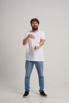 Homem barbudo com uma camiseta branca e uma mão enfaixada posando com remédio hospitalar