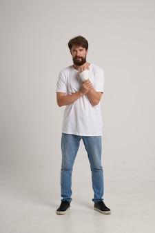 Homem barbudo com uma camiseta branca e uma mão enfaixada posando com um fundo isolado