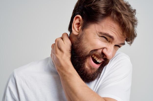 Homem barbudo com uma camiseta branca estresse remédio para dor no pescoço isolado fundo