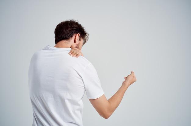Homem barbudo com uma camiseta branca estresse remédio para dor no pescoço tratamento de estúdio