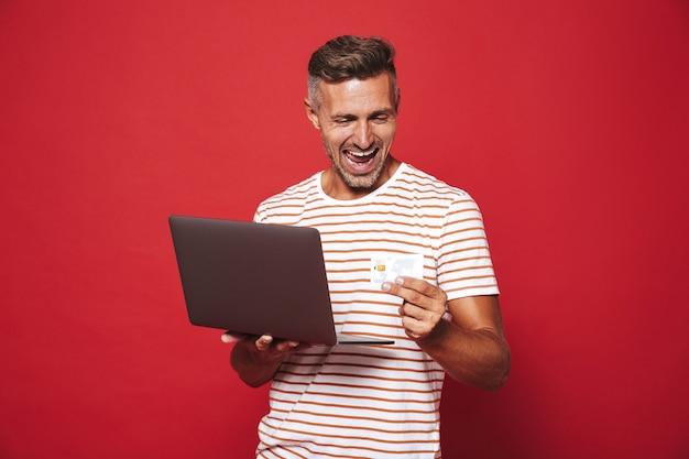 Homem barbudo com uma camiseta listrada sorrindo enquanto segura um cartão de crédito e um laptop isolado no vermelho