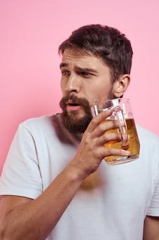 Homem barbudo com uma caneca de cerveja em um espaço rosa emoções divertidas vista recortada de uma camiseta branca bêbada