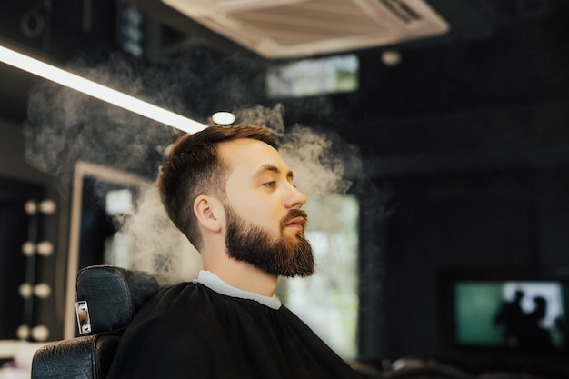 Homem barbudo com uma capa preta de corte de cabelo na barbearia preta