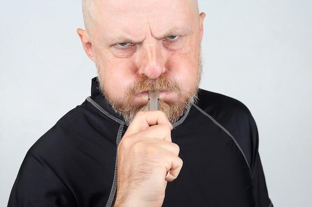 Homem barbudo com uma jaqueta preta soprando um apito