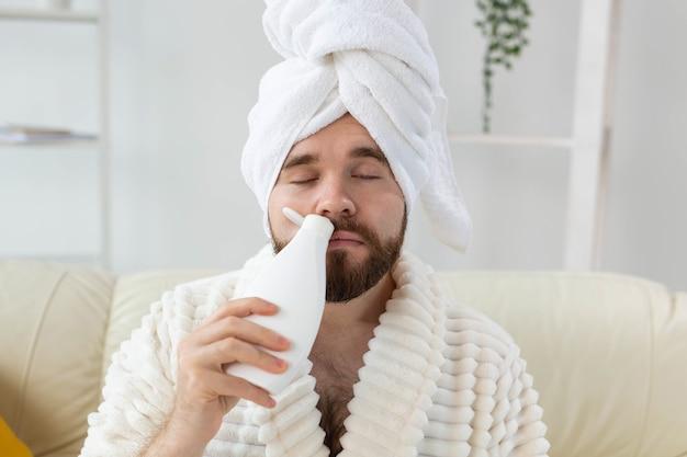 Homem barbudo com uma toalha na cabeça aplicando creme de loção corporal. o cara sorri quando sente o cheiro do creme de loção