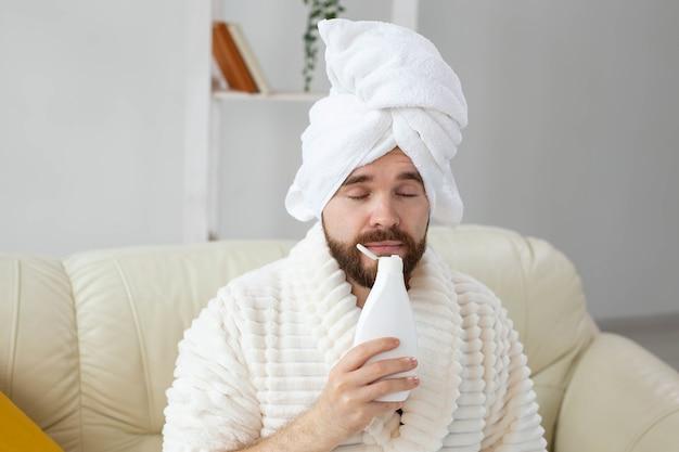 Homem barbudo com uma toalha na cabeça, aplicando o creme de loção corporal. cara sorri ao sentir o cheiro do creme de loção na mão. spa, corpo e pele cuidados para o conceito de homem.