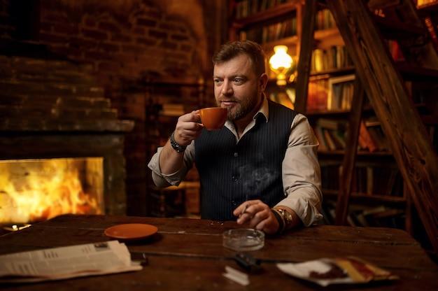 Homem barbudo com uma xícara de chá fuma um cigarro, estante e rico interior de escritório em segundo plano. cultura de fumar tabaco, sabor específico. lazeres de fumantes masculinos