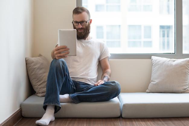 Homem barbudo concentrado sentado no travesseiro e usando o tablet
