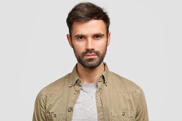 Homem barbudo confiante com cabelo escuro, expressão facial séria, pensa no futuro emprego, vestido com uma camisa da moda